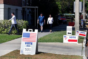 In this March 17 file photo, voters head to a polling station to vote in Florida's primary election in Orlando. Six U.S. citizens living in Guam and the U.S. Virgin Islands have filed a federal lawsuit, challenging federal and state laws that deny their voting rights.