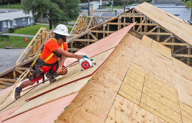 Jose Laguna rips sheets of plywood while decking one of the three buildings at the Tuscawilla Apartments project being built on the corner of Northeast Sanchez Avenue and Northeast Fourth Street on Tuesday. They hope to have the $3.1 million project completed by December.