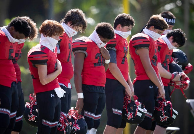 Jupiter Christian high school football players mark a moment of silence Friday for the 9/11 anniversary before their game against Berean Christian.