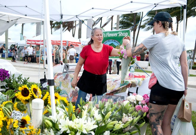 Flashback to October 2019: Teresa Carlisle sells a bouquet to Laura Nave at West Palm Beach's weekly GreenMarket.  [MEGHAN MCCARTHY/palmbeachpost.com]
