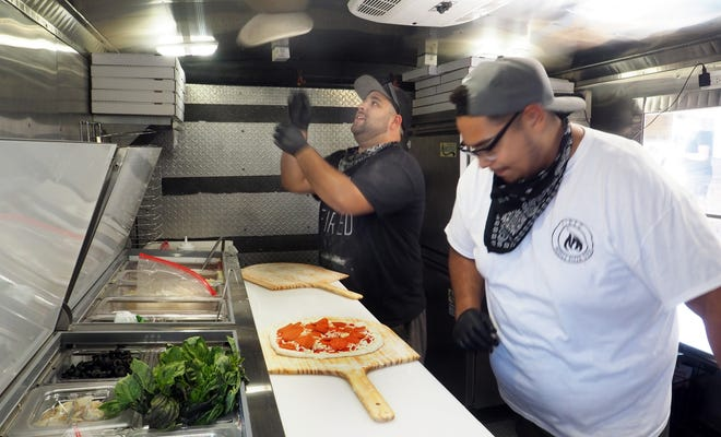 Daniel Correa flips pizza in the air while Jorge Flores finishes up another in the Fired Mobile Pizza Oven, which can cook pizza in 90 seconds. Fired will be serving up pizza outside the Idol Beer Works in Lodi on Sunday.