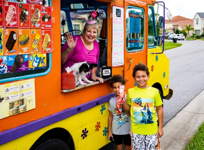 Tammy Hauser waves from the window of The ChillMobile, a mobile ice cream enterprise she started after pandemic restrictions brought her trolley car tour business to a halt.