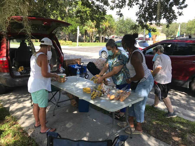 JoOni Jones (second from right), leads volunteers from the Multicultural Health Institute in distributing food outside the La Mirada Gardens in Bradenton.