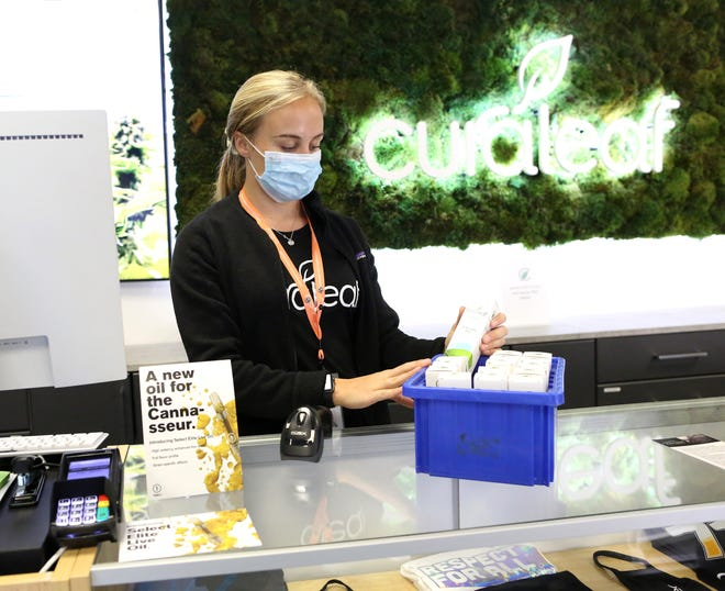Brianna Herrin, a dispensary associate, pulls out some new medical cannabis vaping products to inventory at the Curaleaf cannabis dispensary off SW 34th Street, in Gainesville on Thursday.