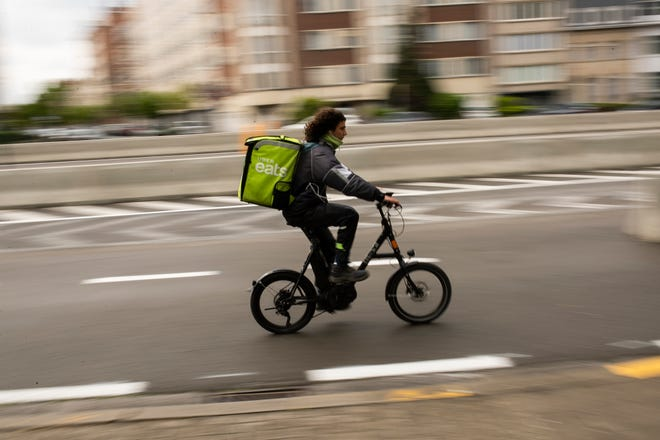 A food delivery carrier rides a bicycle.