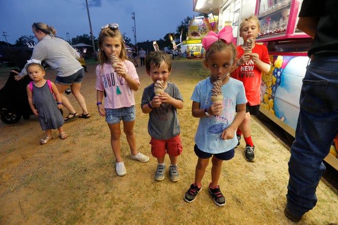 Stella Weber, 6, Gabe Anthony, 3, and Lexi Scott, 5 eat ice-cream at the West Alabama Fair at Sokol Park in Northport, Ala Wednesday, Aug. 29, 2018. [Photo/Jake Arthur]