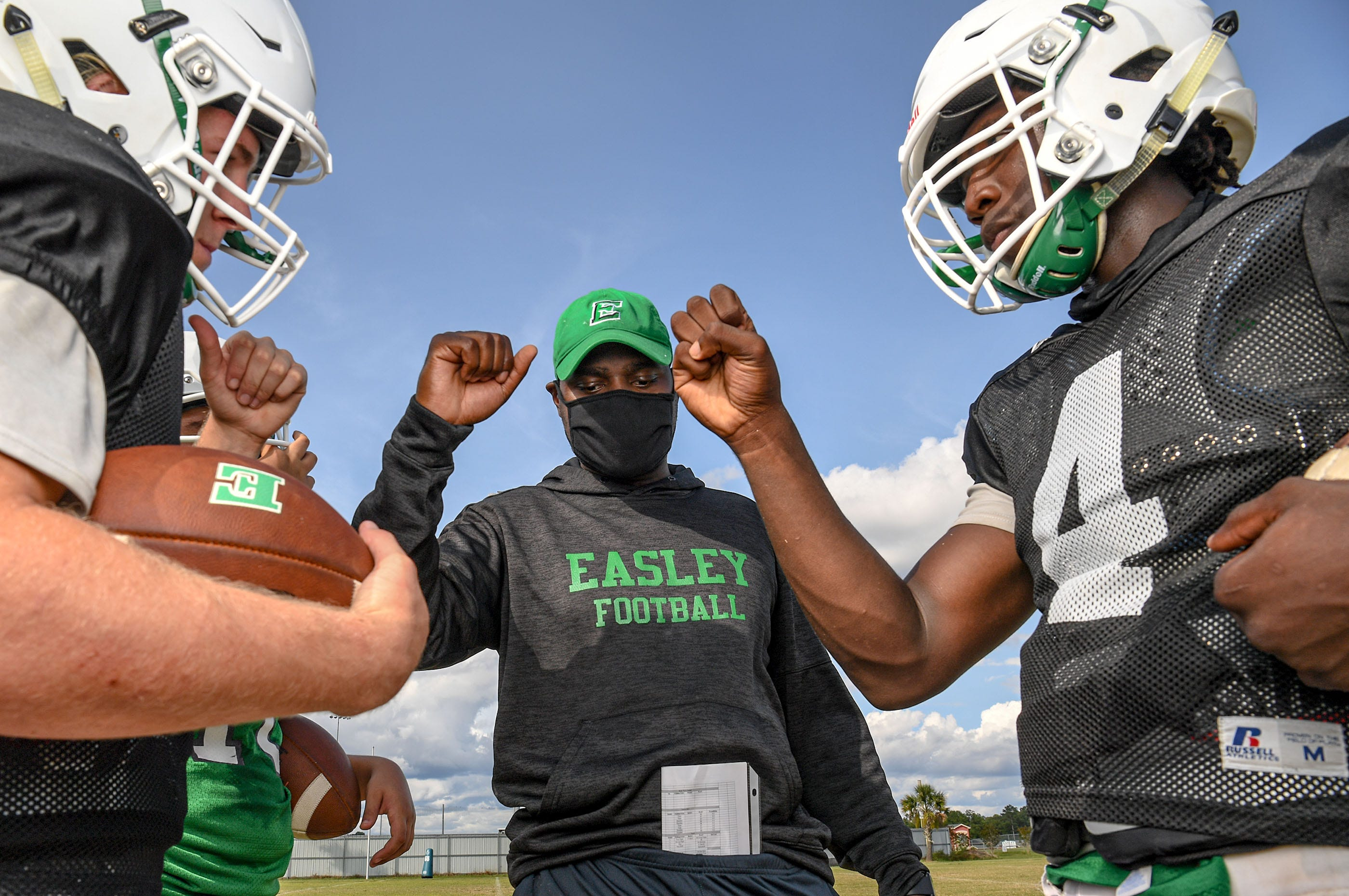 Easley football quarterbacks Kasten Harvey, left, and A.J. Brown break from a huddle with Head Coach Jordan Durrah before a drill in Easley, S.C. September 2020.