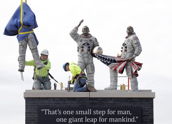 Miron Construction's Chris Button, left, and Garrett Cooper install bronze figures of astronauts Neil Armstrong, Buzz Aldrin and Michael Collins at the Appleton International Airport on Friday. The bronze sculpture commemorating the 1969 moon landing was placed in the center of a new roundabout on Challenger Drive at the airport's entrance.