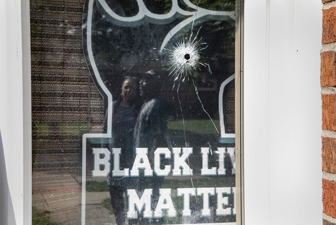 Candace and Eddie Hall stand in their front yard reflected in their front window that was shot through in Warren. The couple and their children have been victims of a hate crime after a suspect flattened their car tires, threw a rock through their window and shot at a Black Lives Matter sign through the family front window leaving six shell casings as evidence. The Warren Police hold a press conference on Sept. 11, 2020.