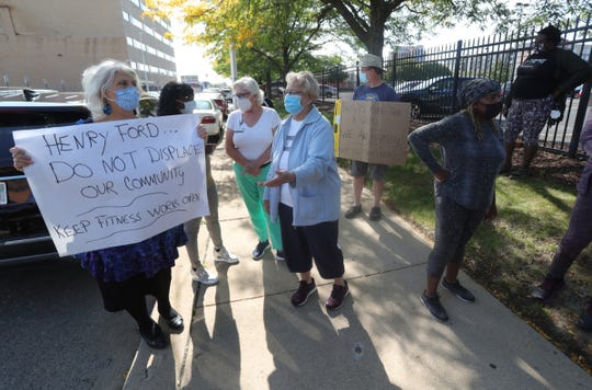 Gym members and employees gathered Friday in front of Detroit's FitnessWorks gym, which is closing because Henry Ford Health System is taking over the space.