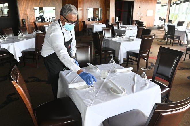 Pelayan Eddie Henderson menyiapkan meja di Joe Muer Seafood yang terletak di Renaissance Center di Detroit pada hari Jumat, 11 September 2020 karena Covid-19 telah merugikan bisnis.