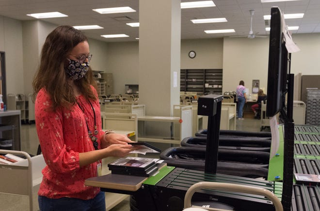 Evansville Vanderburgh Public Library Customer Experience Representative Sarah Renahan processes library holds at the Central location in downtown Evansville Friday afternoon, Sept. 11, 2020.