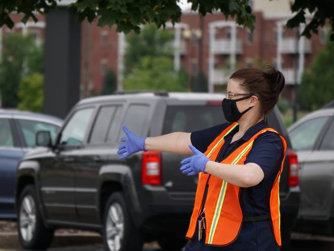 Amy Woolf, a job service career counselor for the Department of Workforce Development, directs people on July 15 at a drive-thru job fair in Oshkosh. The department is hosting a series of more job fairs using the drive-thru format on Thursday.