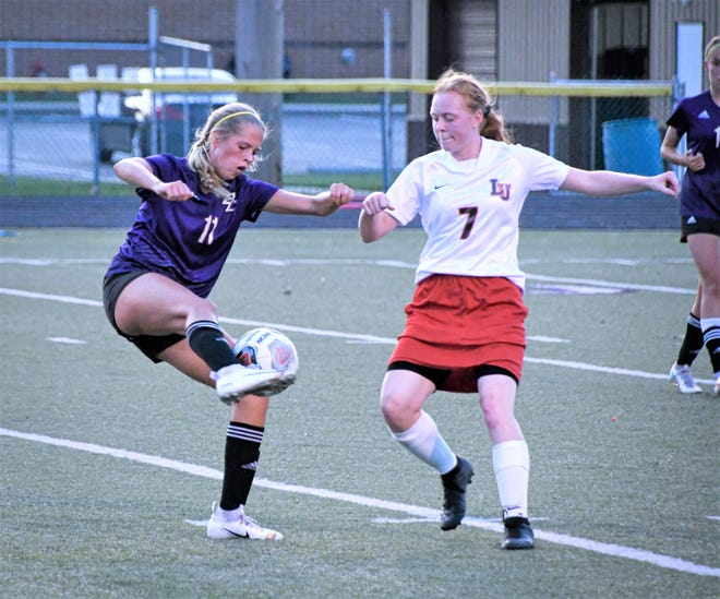 Bloom Carroll sophomore Sophia Haughn attempts to keep the ball away from Liberty Union senior Captain Rachel Miracle at Carl Fell Field.  The Bulldogs won 5-0.