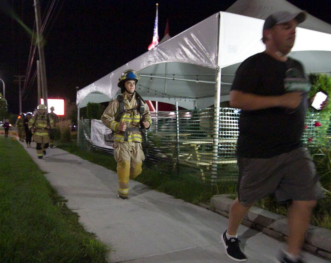 Brighton Area Fire Authority firefighters dressed in their turnout gear, joined by supporters, run north on Grand River Avenue Friday, Sept. 11, 2020, starting their annual run at Station 31, the location of a 9/11 memorial. The annual event commemorates the heroic actions of first responders on Sept. 11, 2001.