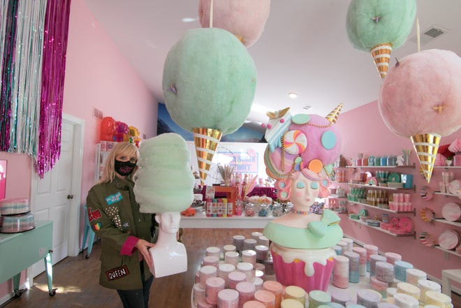 Spun Sugar Shoppe owner Mandy Tamborini holds a lime-flavored cotton candy hairdo inside her recently opened Green Oak Township business Friday, Sept. 11, 2020.