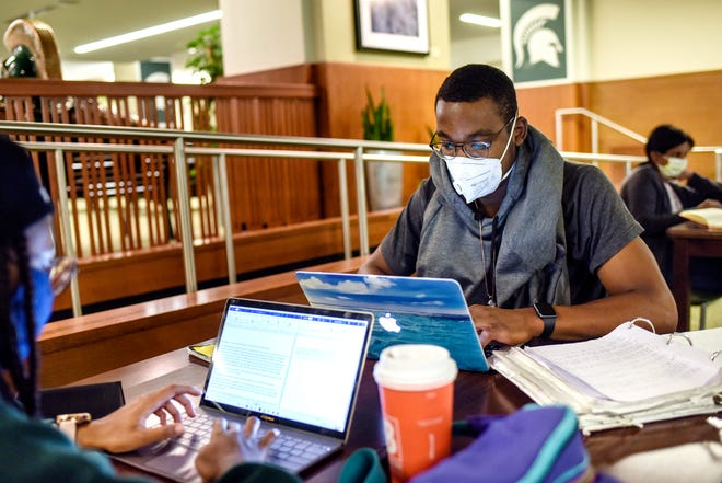 Michigan State University juniors Vontae Jones, right, and Amina Johnson wear masks while studying inside the MSU Union on Friday, Sept. 11, 2020, on the MSU campus in East Lansing. Jones is studying advertising management and Johnson is studying psychology.