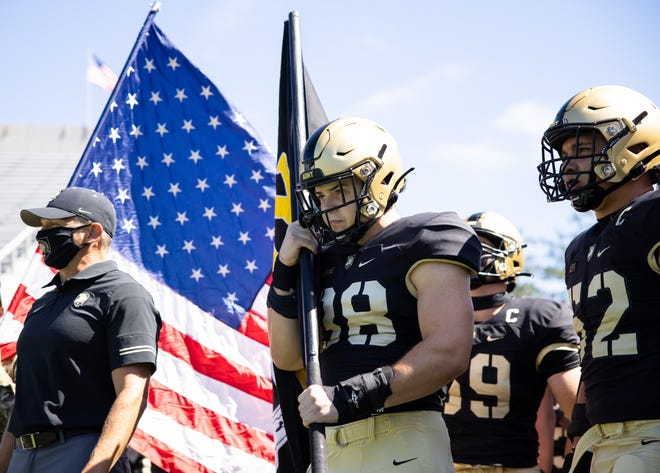 Fabrice Voyne carries the Army black flag prior to Army's season football opener on Saturday, Sept. 5, 2020 at Michie Stadium in West Point, N.Y.