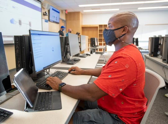 """Marcus Henry works on his computer during an """"Intro to Cybersecurity"""" class at the University of West Florida in Pensacola on Thursday."""