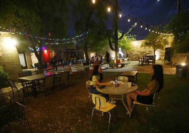 Andrea Leal (izquierda) y Justine Cardenas conversan mientras disfrutan unas bebidas durante el primer día de reapertura en Thunderbird Lounge en Phoenix el 27 de agosto de 2020.