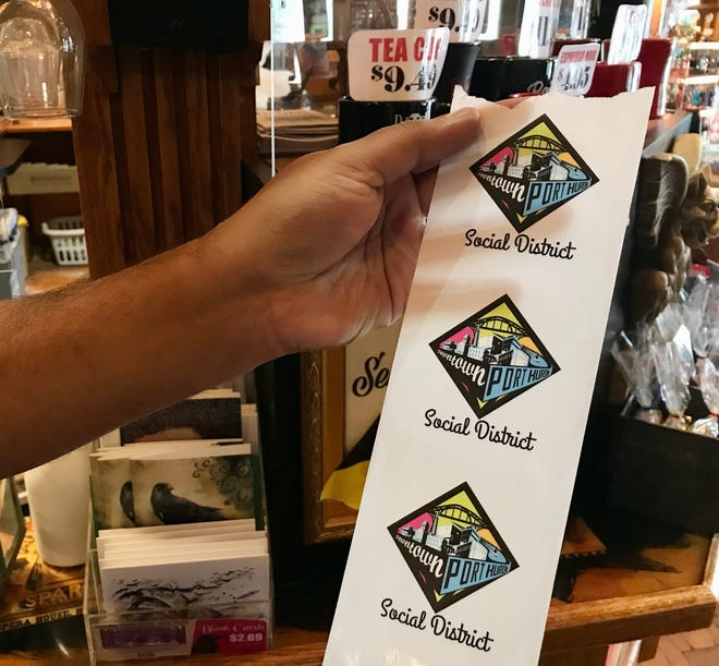 Raven Cafe co-owner Sadaat Hossain holds social district stickers which the cafe will put on alcoholic beverages it serves to customers to enjoy in Port Huron's downtown social district on Sept. 11, 2020.