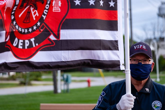 Port Huron Police VIPS volunteer Joe Hayes holds a flag honoring fire departments that responded to the World Trade Center while standing in silence in honor of 9/11 Friday, Sept. 11, 2020, at the International Flag Plaza in Port Huron. This year's annual memorial service was canceled due to the coronavirus pandemic.
