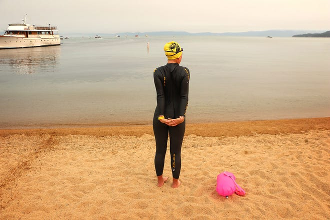 "Andi Bertolina stretches before undertaking the swimming portion of her ""Tahoe Trifecta"" attempt out of South Lake Tahoe on Sept. 10, 2020. The trifecta consists of three laps around Lake Tahoe. First, a twelve day/six mile per day swim around the perimeter of the lake, then cycling around the lake and eventually running around the lake in consecutive days."