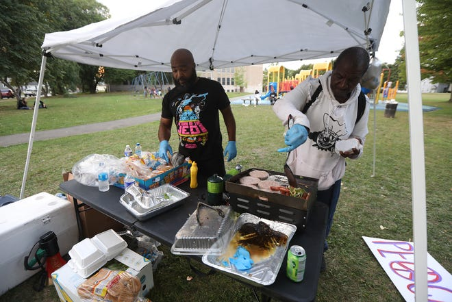 Abdul Hadi El Bey and Kent Mathis, both with Community Justice Initiative, cook up food to give to anyone free of charge. The group held a march starting on Thurston Rd. and ended it at School 4 on Dr. Samuel McCree Way in Rochester, NY, Sept. 10, 2020. The group's goal is to stop the violence and support the community, by holding themselves accountable for each other. They hold a free meal giveaway every two weeks at different locations.