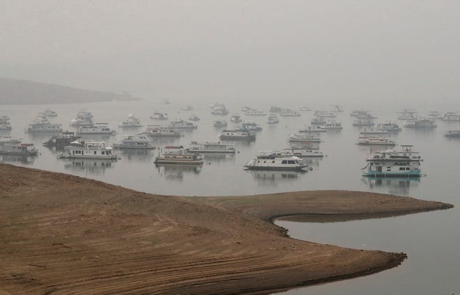 A heavy haze hangs over houseboats moored in Lake Oroville during the Bear Fire in the North Complex on Thursday, Sept. 10, 2020.
