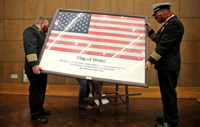 San Angelo Fire Department Fire Chief Brian Dunn, left, and SAFD Assistant Chief Patrick Brody, right, set up the Flag of Honor prior to the annual 9/11 Memorial Ceremony at the San Angelo Museum of Fine Arts on Friday, Sept. 11, 2020.