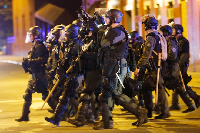 Police in riot gear advance on protesters as they attempt to clear the streets in Richmond in May. Virginia lawmakers are pushing for changes to make it easier to decertify problem police officers and more difficult for them to hop from department to department.
