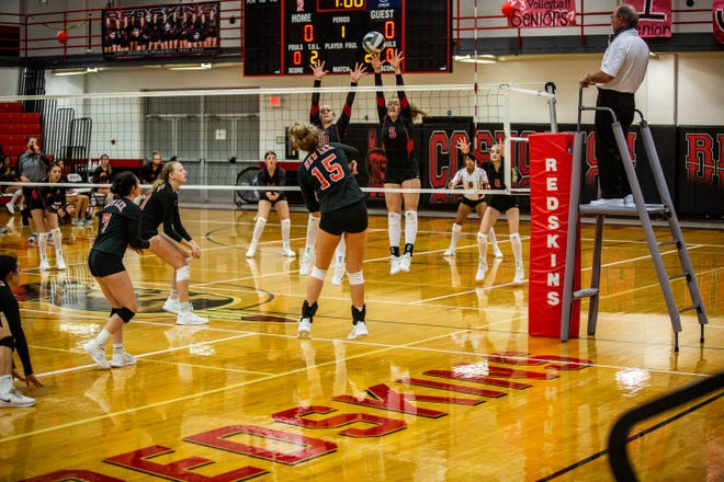 Coshocton's Hailey Helter and Kindall Shaw go up high for the block against New Lexington's Bailee Agriesti on Thursday night. The Panthers won in three sets.
