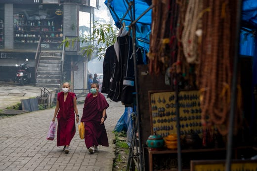 Exile Tibetan Buddhist monks wearing masks as a precautionary measure against the coronavirus walks in a deserted market area in Dharmsala, India, Friday, Sept. 11, 2020. India's coronavirus cases are now the second-highest in the world and only behind the United States.