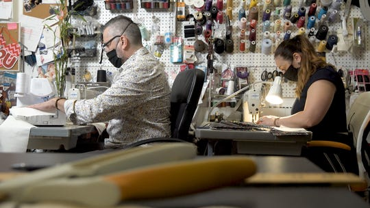 Adrienn Braun works with her husband Emilio Mazzucotelli to create face masks using extra fabric in her store.