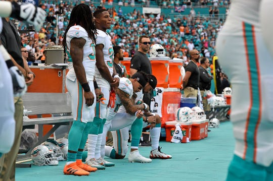 Former Miami Dolphins wide receiver Kenny Stills (10) and Miami Dolphins wide receiver Albert Wilson (15) kneel during the national anthem prior to the game against the Detroit Lions at Hard Rock Stadium.