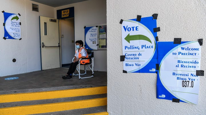 A poll worker sits outside a poling centre during Florida Primary Election amid the coronavirus pandemic, in Miami Beach, Florida on August 18, 2020. - In Miami-Dade, voters are casting ballots to elect Miami-Dade's mayor, School Board seats, Miami-Dade state attorney and Judges. The polling stations with secure drop boxes will allow voters to drop off the state's Primary Election Vote-By-Mail ballots and skip any voting lines as people are looking alternatives to vote and stay healthy during the coronavirus pandemic. (Photo by CHANDAN KHANNA / AFP) (Photo by CHANDAN KHANNA/AFP via Getty Images) ORIG FILE ID: AFP_1WL3LG