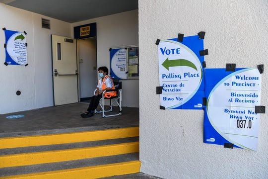 A poll worker sits outside a poling center in Miami Beach, Florida on August 18, 2020.