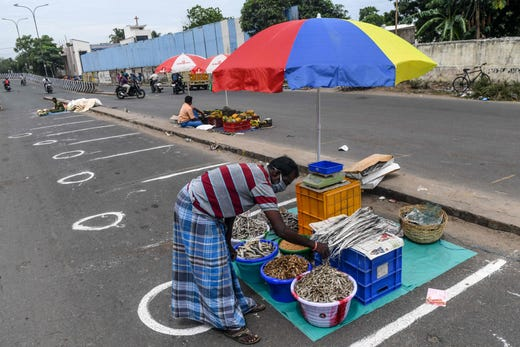 A vendor sets up his stall in marks painted on the floor for social distancing as he waits for customers at the 100-year-old Pallavaram Friday market that has reopened following the state government's decision to ease the measures imposed against the Covid-19 coronavirus, in Chennai on September 11, 2020.
