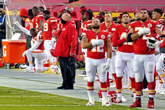 Kansas City Chiefs defensive end Alex Okafor (57) kneels for the national anthem before the game against the Houston Texans at Arrowhead Stadium.
