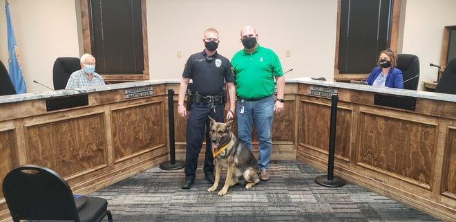 Ardmore Mayor Doug Pfau presents a medal to APD K-9 Officer Jared Johnson and his K-9 Boss, during a city commission meeting, honoring Boss on his retirement from the police department.