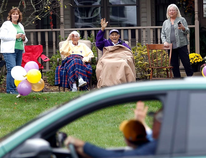 Ruth and Fred Martinelli enjoy the drive-by celebration Friday for Ashland University's 100th anniversary of their first football game against Heidelberg 100 years ago on Sept. 25 in front of College Football Hall of Fame football coach Fred Martinelli's home.