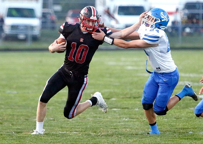 Crestview's Ross Kuhn (10) stiff arms Western Reserve's Carson Roe (24) on a carry in the second quarter of high school football action on Friday at Crestview High School's Scott Bailey Memorial Field. The Cougars won, 35-13.
