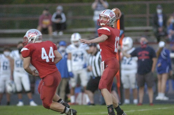 Loudonville's Logan Huffman (13) fires a pass during high school football action against Tuslaw on Friday night at Redbird Stadium. The Redbirds won, 28-6.