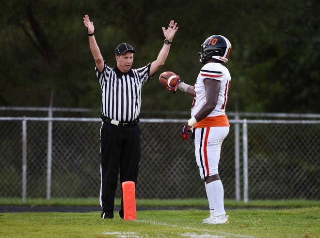 Beaver Falls' Joshua Hough hands an official the ball after scoring a touchdown during Friday's game at Riverside.
