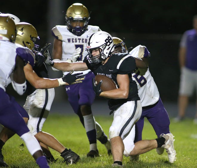 South Side's Andrew Moots (99) attempts to get through Western Beaver's defensive line and gets corralled by Daquan Bradford (56) during Friday nights game at South Side High School.