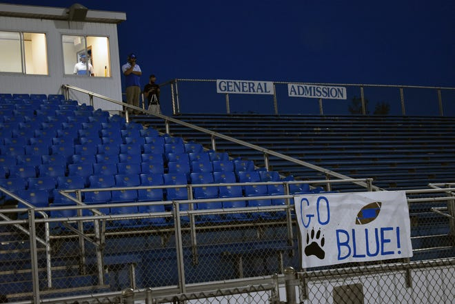 Friday's evening sky was Wolverine blue as it blended into the empty stands at Helling Stadium. Despite the starkness, there were plenty of fans gathered outside the stadium fence to watch the game.