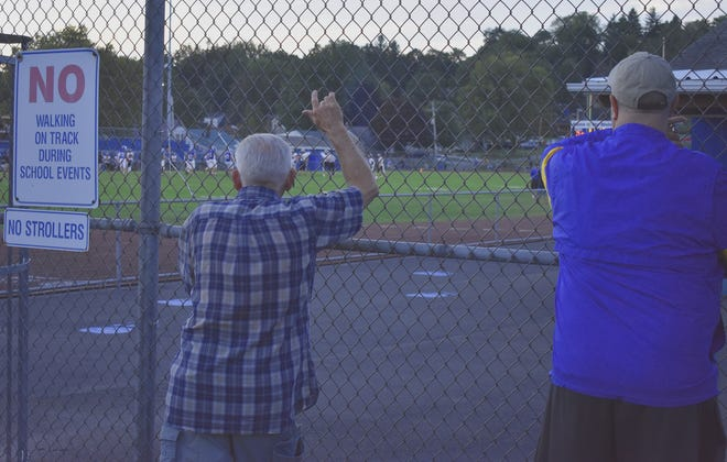 Two spectators watch the Mohawk-Ellwood City game Friday through the chain-link fence at Helling Stadium. Fans were not permitted inside the stadium due to COVID restrictions. However, they set up chairs along the perimeter of the stadium to support their teams.