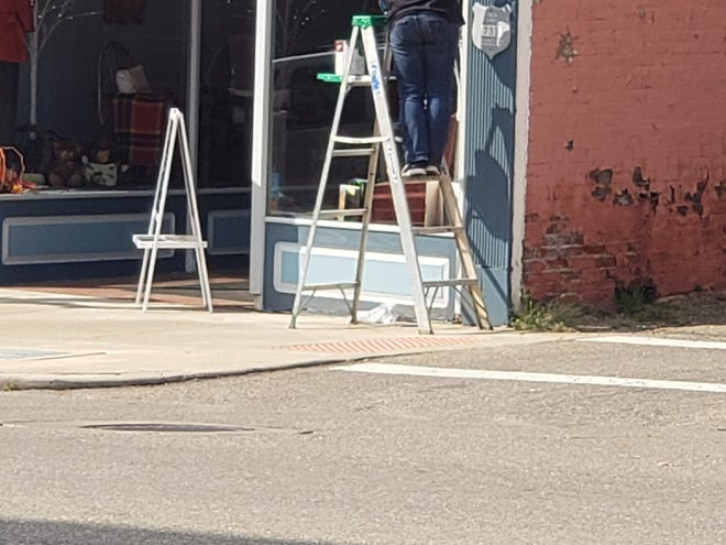 Jennifer Patterson helps her mom Mary Jo Rogers prepare to open her new business,  MJ's Closet, by putting a fresh coat of paint on the storefront.