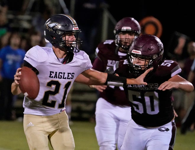 Trinity Christian's Jordan Rivera (50) chases down Leesburg First Academy quarterback Nicolas Jackson (21) during Friday night's game.
