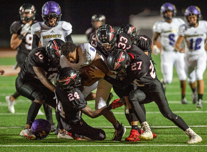 Fort Osage defenders Daniel Tapusoa (16), Gavin Gilliam (24), David Jacquez (33), Ryan Thorpe (27) and Larenzo Fenner (1) all swarm for a gang tackle on North Kansas City's J'Len Friar as Friar loses his helmet during Fort Osage's 19-14 win Friday.